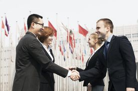 Four smiling business people meeting and shaking hands in Beijing