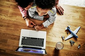 child and parent on laptop