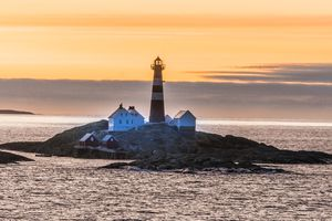A lighthouse on a rocky island in the ocean at sunset.