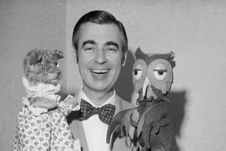 Mister Rogers with owl and cat puppets, black and white photograph.