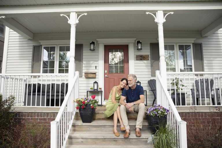 couple sitting in front of home