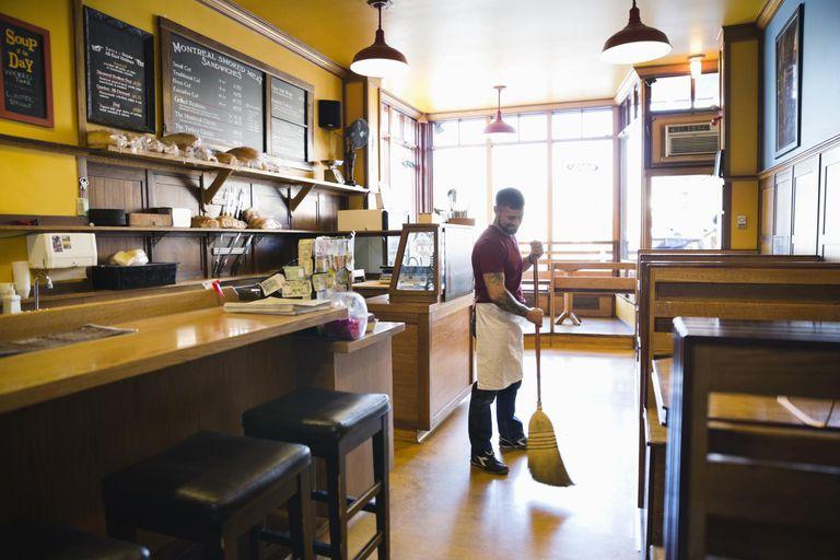 Male deli worker sweeping floor in restaurant