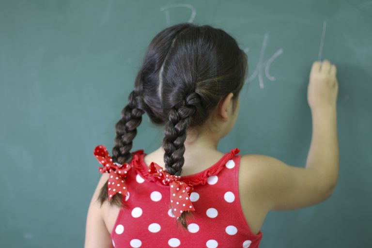 Girl writing on blackboard at classroom