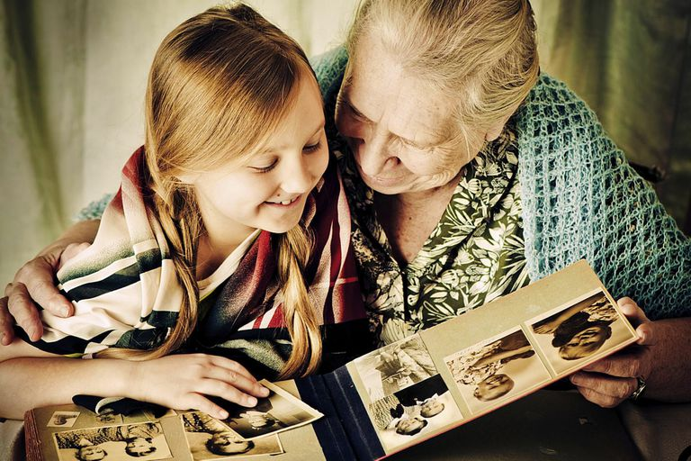 Grandmother shares a photo album with her granddaughter