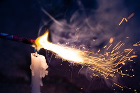 A firecracker being lit with a candle