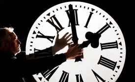 Man touching the hands of a clock
