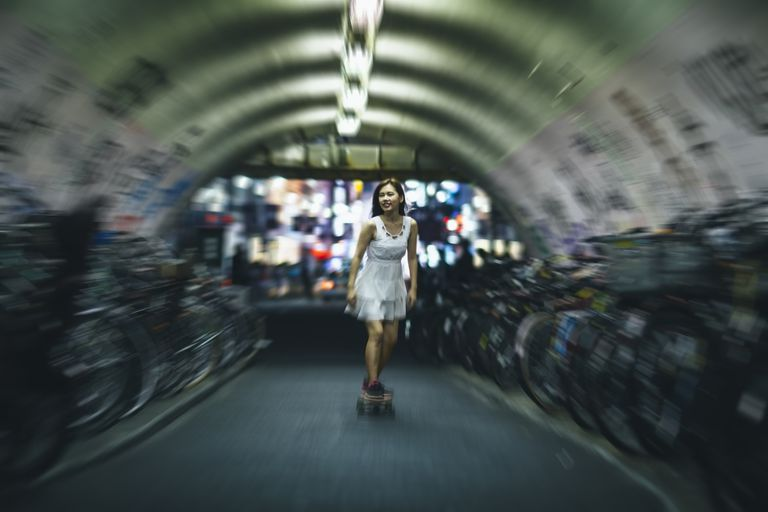 Young Japanese woman riding skateboard in tunnel next to bikes