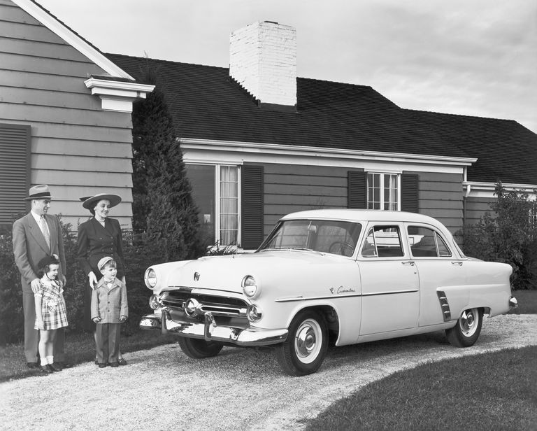 1950s image of a family in driveway with their Ford