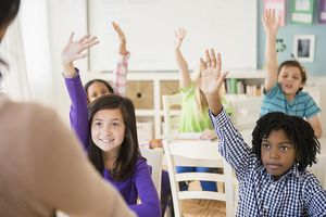 Well behaved students raising hands in class