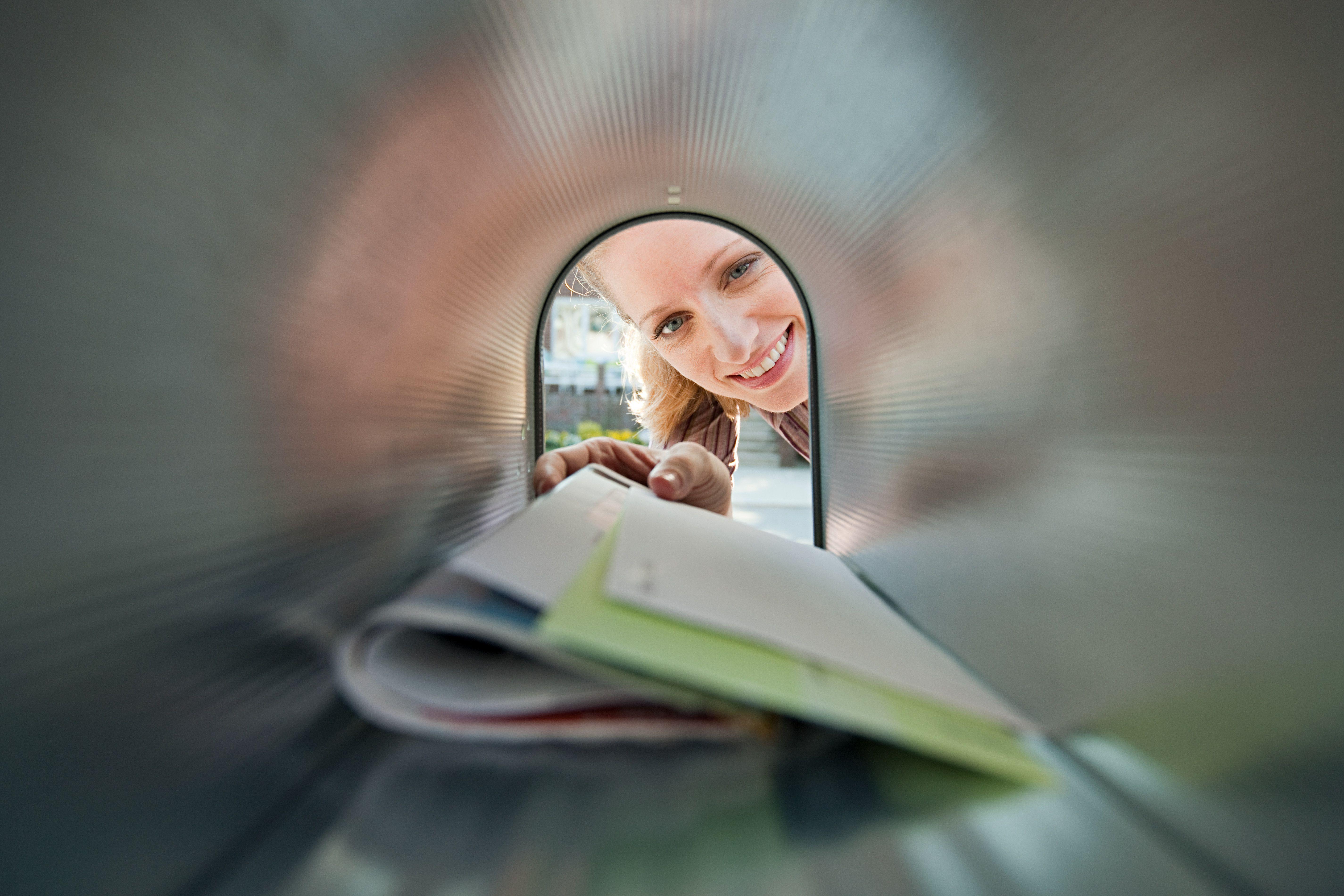 Frau, die Post vom Briefkasten sammelt