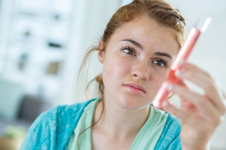Teenage girl holding a test tube during science class