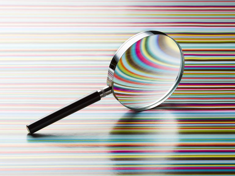 Magnifying glass leaning on striped background