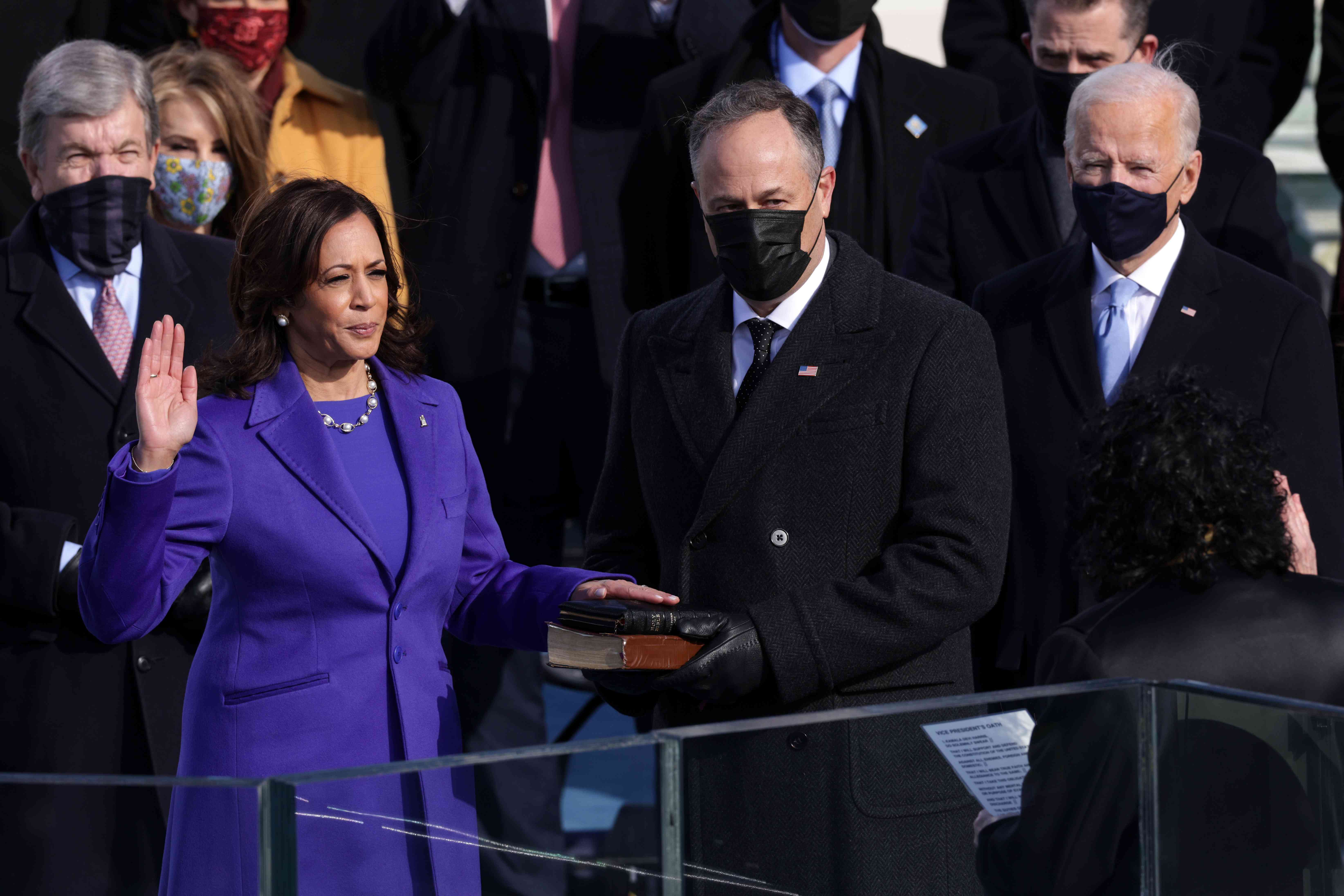 Kamala Harris takes the oath of office as Doug Emhoff holds her Bibles