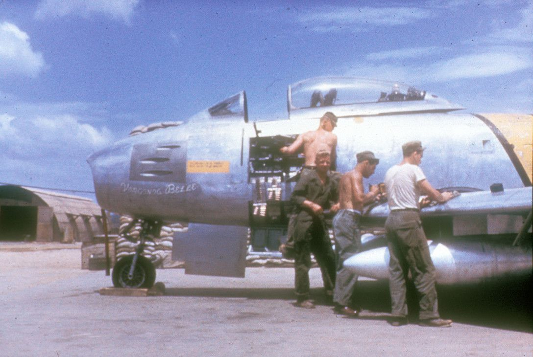 Armorers alongside a F-86 Sabre with a side panel removed.