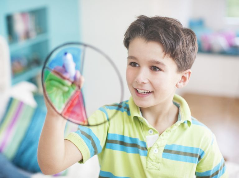 Boy drawing pie chart on glass wall