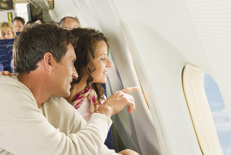 Una pareja de muchachos miran por ventanilla de un avión