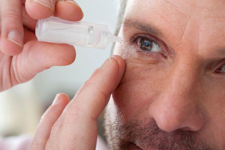 man applying eye drops into eye
