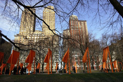 The Orange Gates flutter in Central Park with tall, masonry city buildings in the background outside the park
