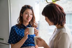 Mid adult daughter and senior mother talking while having coffee