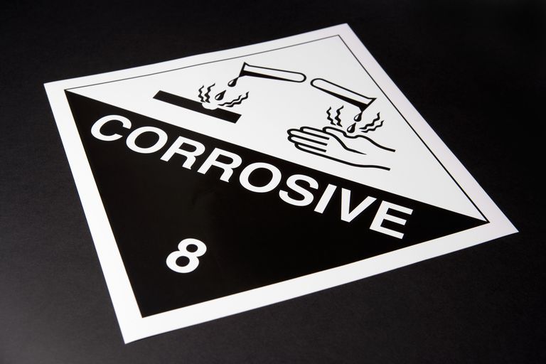 Corrosive warning sign on a black background.