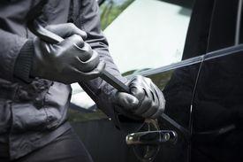 A man breaks into a car with a crowbar