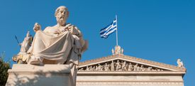 Statue of Plato in front of a building with the Greek flag against a blue sky.