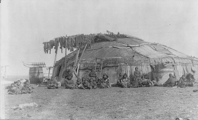 This photograph of a group of Inuit people on St. Lawrence Island in front of their semi-subterranean house was taken by F. D. Fujiwara in 1897. Walrus meat is drying on the rack over the doorway
