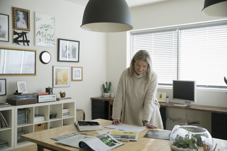 An artist sketches at her kitchen table while looking at magazines