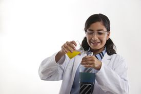 A child scientist pouring one beaker into another