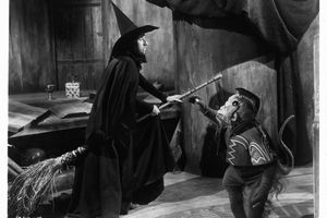 The Wicked Witch on a broom next to her flying monkey in