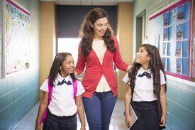 Teacher Walking with Students in School Hallway
