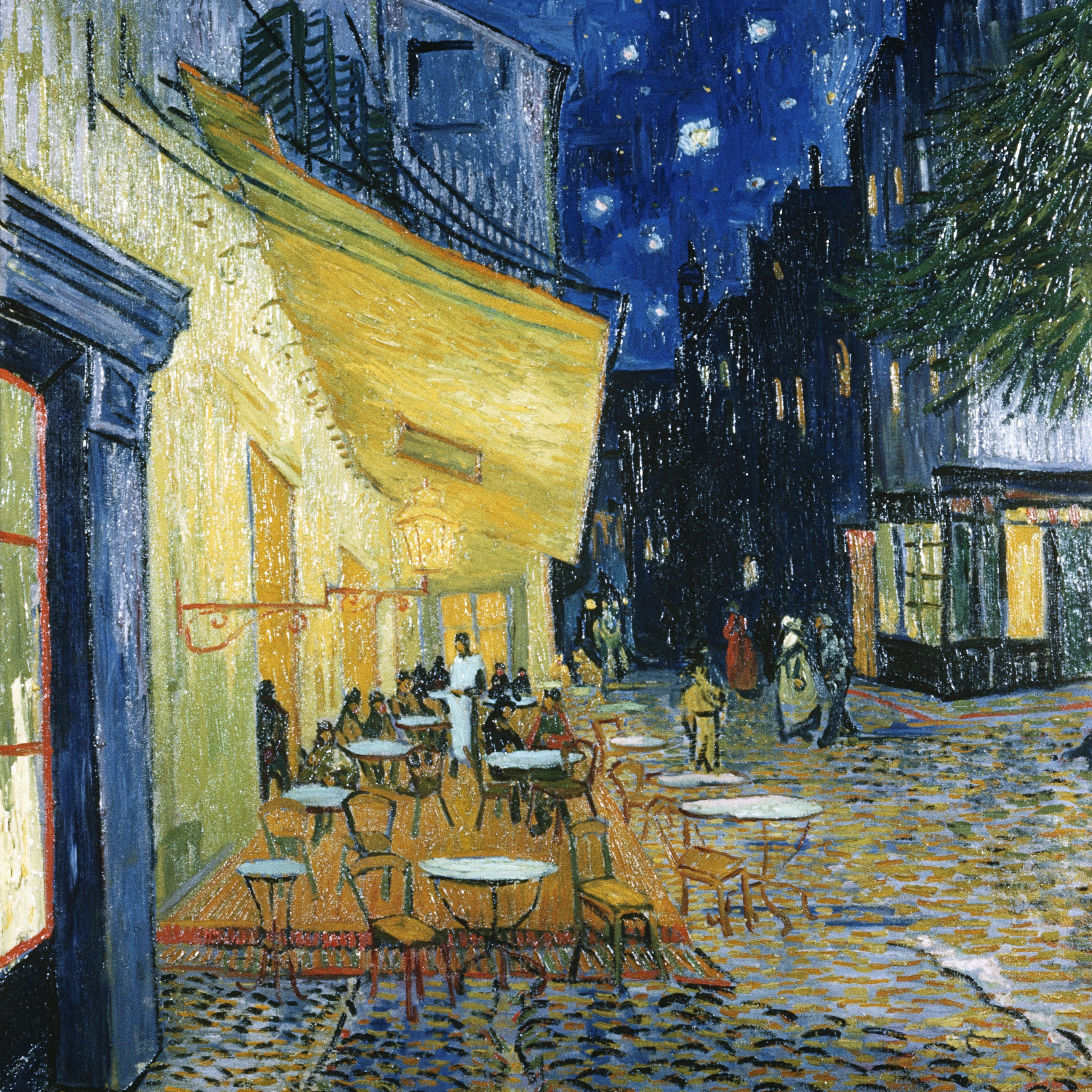 Star-lit sky, yellow awning, empty round tables, and cobbled pavement.