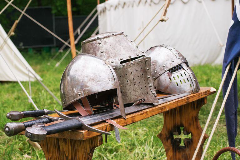 Close-Up Of Medieval Helmets And Swords On Table.