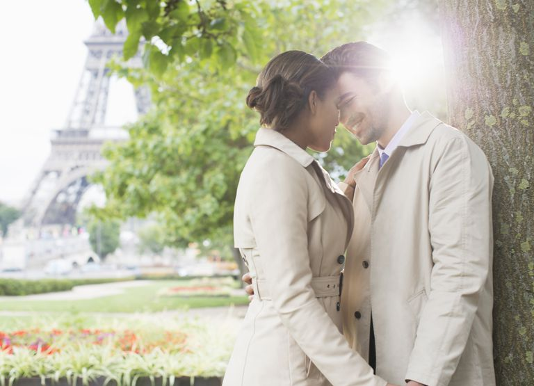 Couple kissing in park near Eiffel Tower, Paris, France