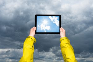 tablet with sunny weather held to stormy sky
