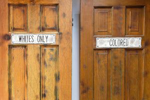"""Doors marked """"whites only"""" and """"colored"""" signal both prejudice and racism. Learn the difference between the two here."""
