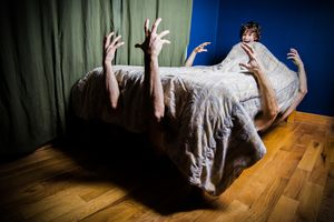 scared child in bed with arms reaching up from benath