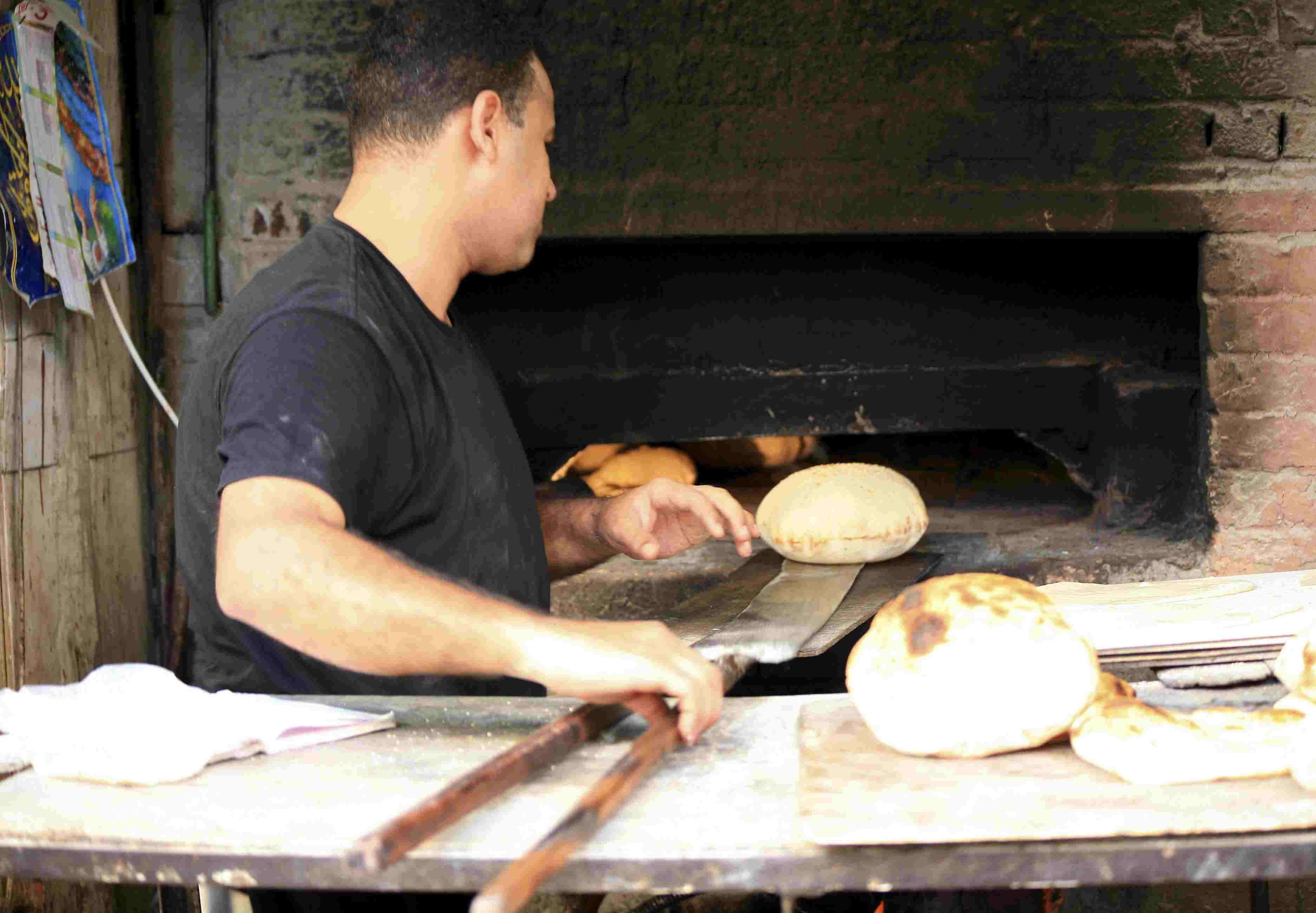 Panadero sacando pan de un horno.