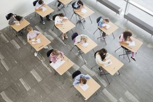A group of students sitting at their desks writing
