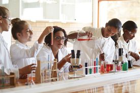 chemists in a lab practicing reactivity of chemicals