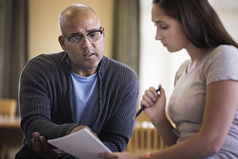 man and woman discussing papers