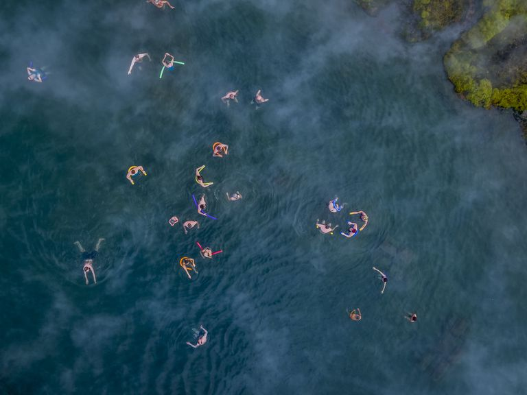 Aerial view of people swimming in a natural hot spring known as The Secret Lagoon, located near the small village of Fludir, a short drive from Reykjavik, Iceland.