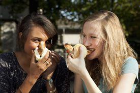 Teenage girls eating Bratwurst