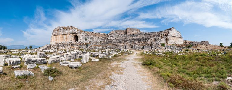 Theater of Miletus against partly cloudy sky.