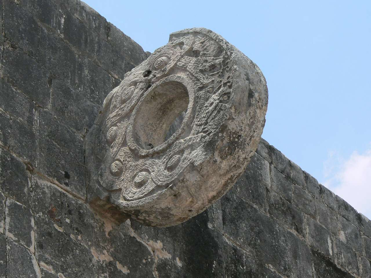 Carved stone ball hoop hanging from wall of ancient ball court