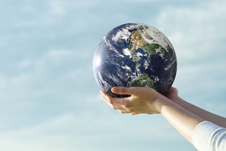 Hands holding a globe with blue sky background