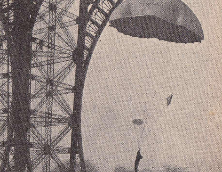 Photograph from early 1900s showing a man parachuting.