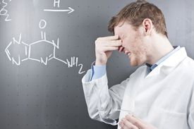 Young male scientist struggling with chemistry equation on chalkboard
