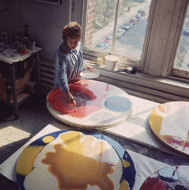 woman painting circular canvases with varying shapes and colors.