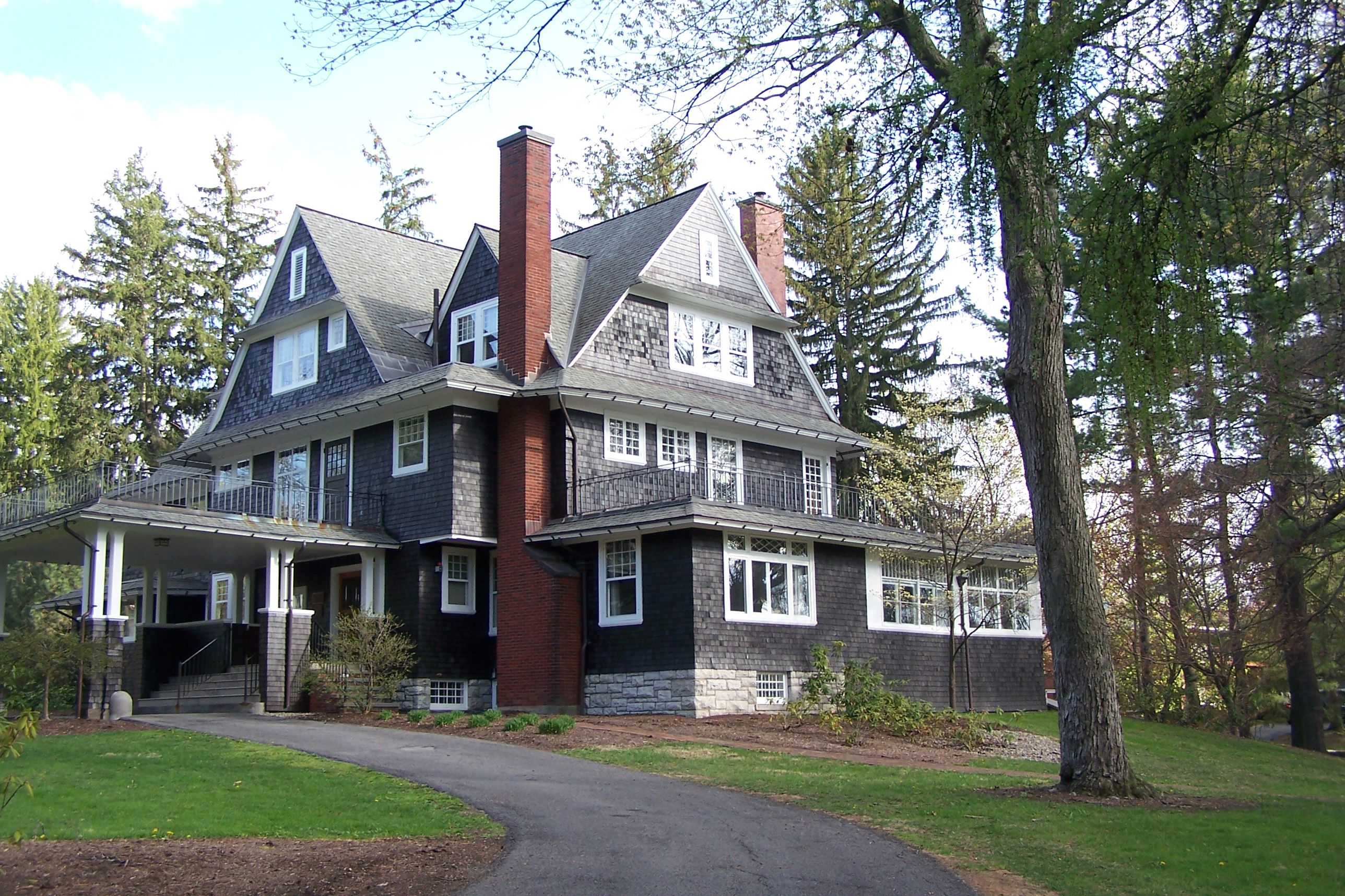 large gray house with tall red chimneys, multiple gables with windows up to a fourth level, side porch extends to car port
